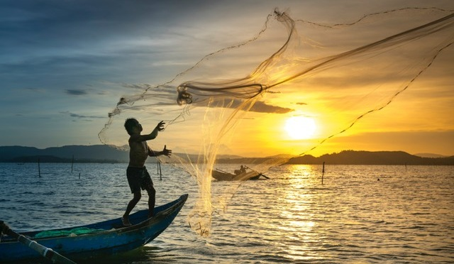 Fishermen throwing a net while standing on a boat