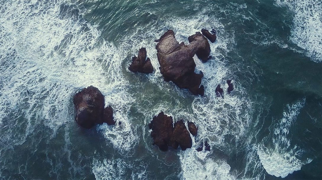 waves of water crashing into a rocky shore