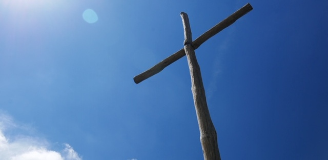 brown wooden cross on a hill