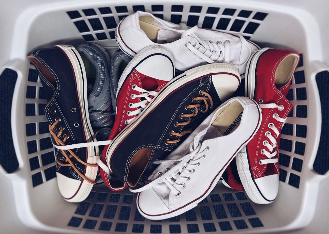 an assortment of sneakers in a laundry basket
