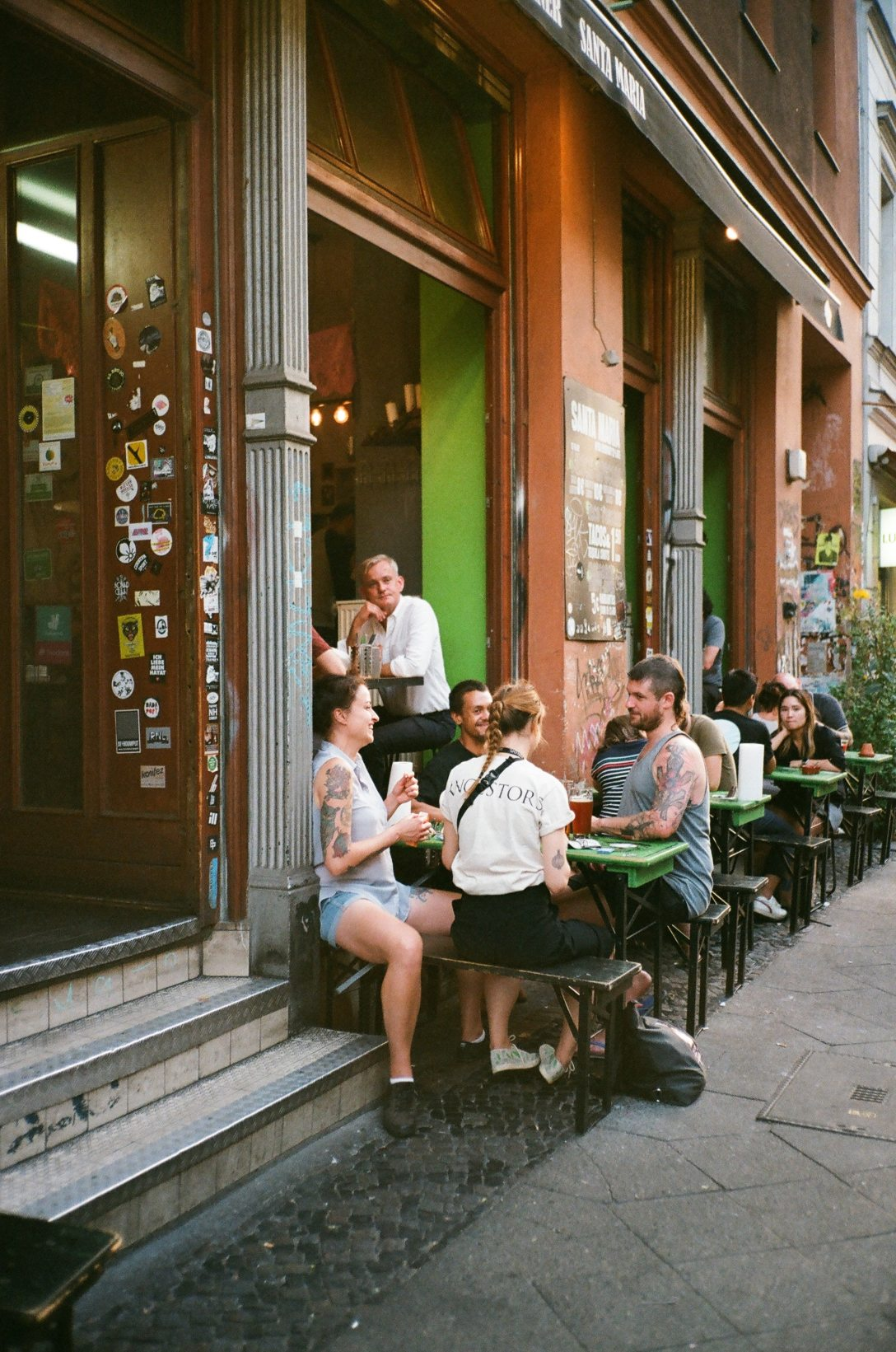 four people sitting at an outdoor table eating