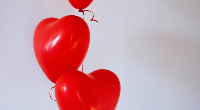 Three red heart-shaped balloons